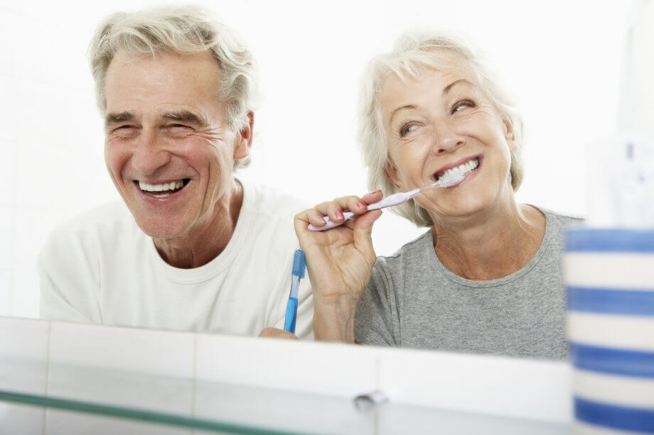 Photograph of an older couple in a bathroom. The woman is brushing her teeth & the man is smiling while looking in the mirror