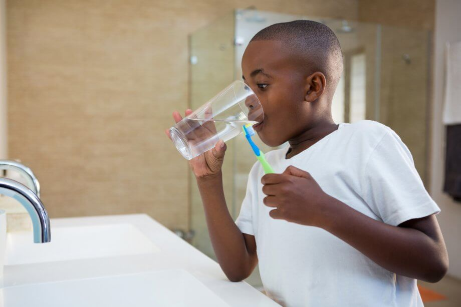 Young boy in front of a bathroom sink with a toothbrush in his hand as he takes a sip from a glass of water.