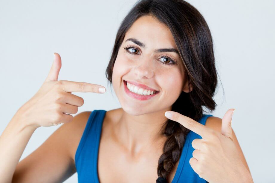 Woman Pointing To Her Smile After Full Mouth Reconstruction